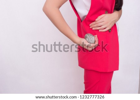 girl on a white background holds a stone in her hand near the kidney, the concept of kidney stones, copy space, disease