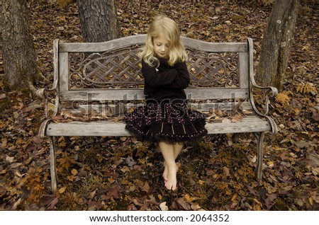 Girl on an antique bench in autumn