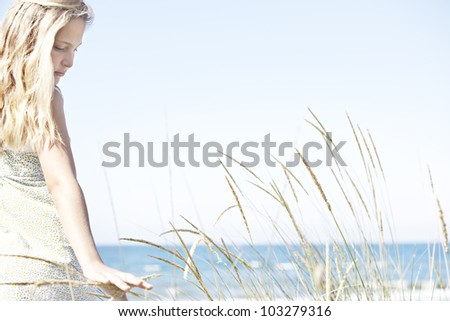 Girl on beach turning and touching long grass against a blue sky.