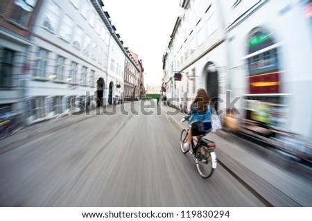 Girl on bike riding fast - motion blur - stock photo