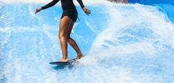 Girl on black swimsuit surfing on wave pool with small board in the island of Phuket, Thailand. Outdoor water sport activity, balance concept