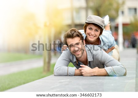 Girl on boyfriend's back laying on public bench
