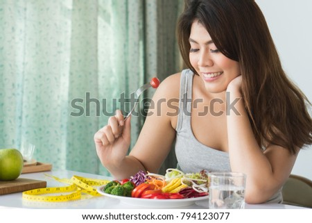 Girl on dieting for weight loss concept. Happy asian woman eating organic salad during dieting session trying to loss her weight.