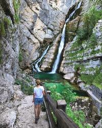 Girl on hiking, back to camera. Alpine waterfall Savica in the nation park Triglav, Slovenia