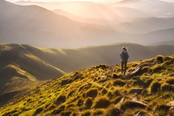 Girl on mountain peak with green grass looking at beautiful mountain valley in fog at sunset in summer. Landscape with young woman on the trail, foggy hills, forest, sky. Travel and tourism. Hiking