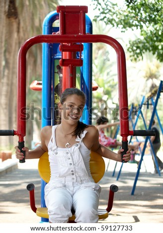 Girl on playground in summer day .