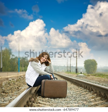 Girl on  railway sitting with her suitcase