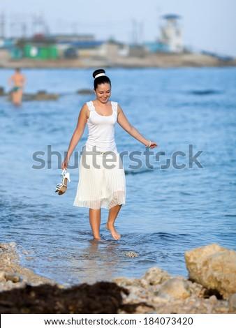 Girl on seashore. Barefoot girl with shoe in her hands walks on water