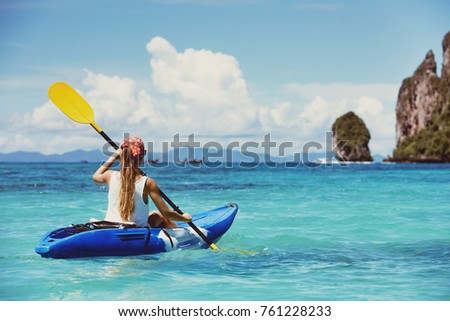 Girl on single kayak or canoe swims at tropical sea bay. Travel or kayaking concept