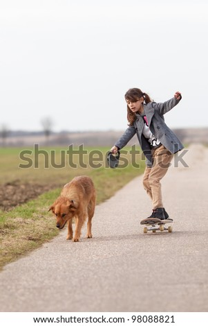 girl on skateboard with a dog at the leash