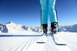 Girl on ski standing on the fresh snow on newly groomed ski piste at sunny day in mountains