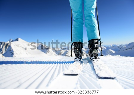 Girl on ski standing on the fresh snow on newly groomed ski piste at sunny day in mountains #323336777
