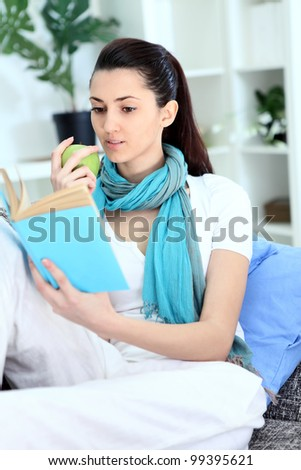 Girl on sofa eating apple and reading book at home