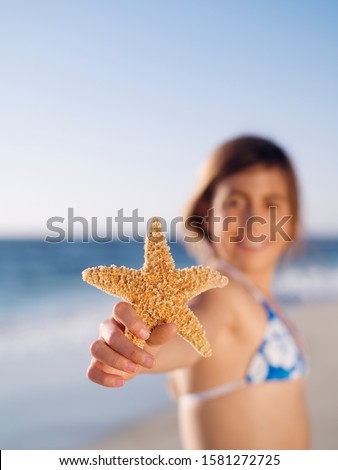 Girl on summer beach vacation holding starfish at camera