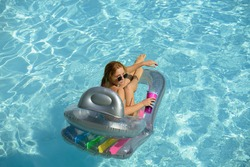 Girl on summertime vacation. Woman swimmsuit. Summertime female on inflatable mattress