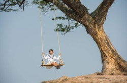 Girl on swings under the trees happily
