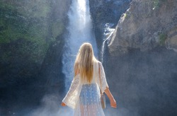 Girl on the background of a waterfall