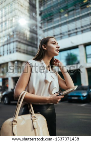 girl on the background of the business center holds the phone and looks with an expectant look into the distance, looking for someone #1537371458
