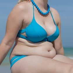 Girl on the beach. Torso of adult woman in blue swimsuit and beads, square composition