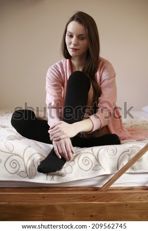 girl on the bed happy dreamy beauty girl hugging her legs while siting in bed against the wooden wall , picture of a girl on the bed happy talking on phone dreamy beauty girl hugging her legs