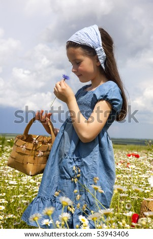 Girl on the field with daisies and poppy