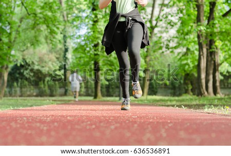 Girl on the red race track running through park