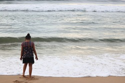 Girl on the sea shore watching waves. Indian girl watching the sea. Girl looking the sea. Lonely girl at the beach.