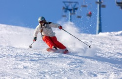 Girl On the Ski. a skier in a bright suit and outfit with long pigtails on her head rides on the track with swirls of fresh snow. Active winter holidays, skiing downhill in sunny day. Woman skier