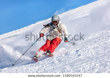 Girl On the Ski. a skier in a bright suit and outfit with long pigtails on her head rides on the track with swirls of fresh snow. Active winter holidays, skiing downhill in sunny day. Dynamic picture Stock fotó ©