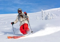 Girl On the Ski. a skier in a bright suit and outfit with long pigtails on her head rides outside of the track with swirls of fresh snow. ski freeride, downhill in sunny day. Heliboarding skiing