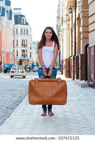 Girl on the street holding a large suitcase.