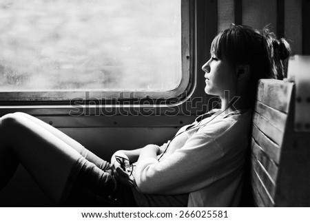 Girl on train. Listen to music. Travel in transport. Sad mood, loneliness. Black and white photo