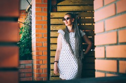 Girl on vacation with braided pigtails gray light shade of Zizi on a Brick and wooden background in a light dress with polka dots