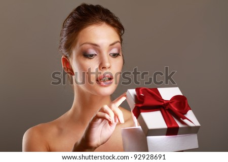 Girl opening x-mass present isolated on grey background