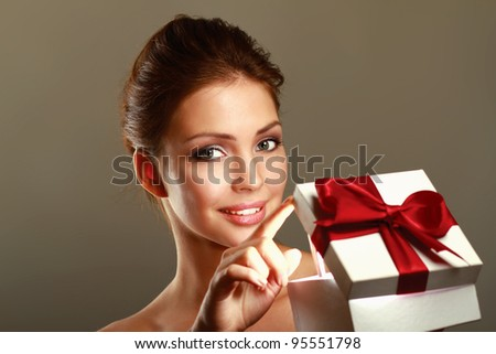 Girl opening x-mass present isolated on grey background - stock photo