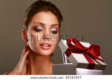 girl openning gift box, isolated on grey background