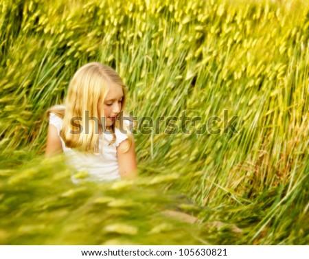 Girl or teen sitting in wheat field looking down