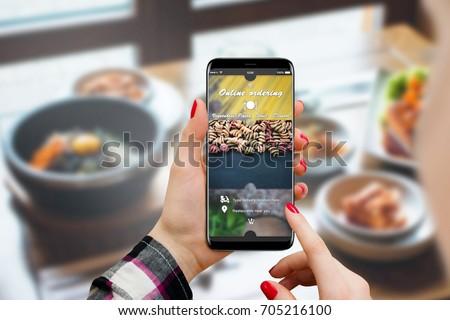 Girl ordering food online on her smartphone, restaurant in background