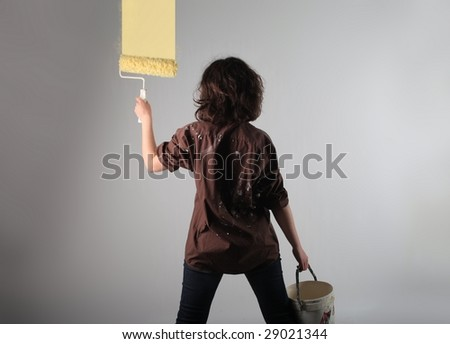 girl painting a wall with a roll