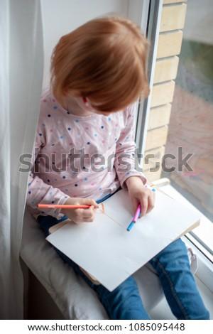 Stock Photo Girl painting sitting on the windowsill