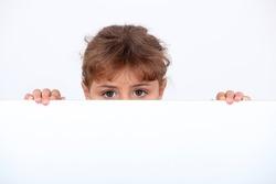 Girl peeking above a board