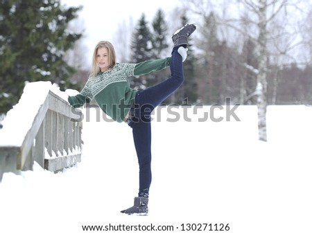 Girl performs gymnastic exercise in the fresh air in the winter