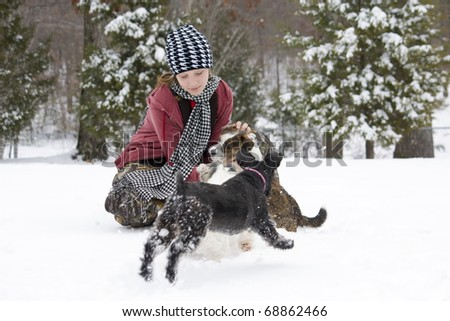 Girl petting her little dogs in the winter snow