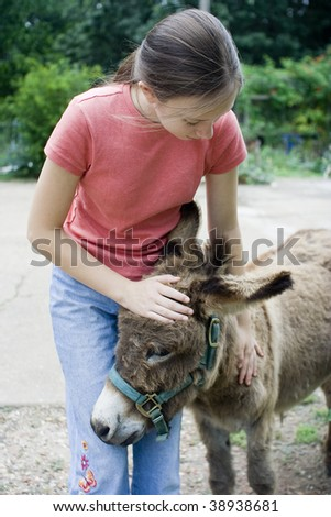 Girl petting miniature donkey