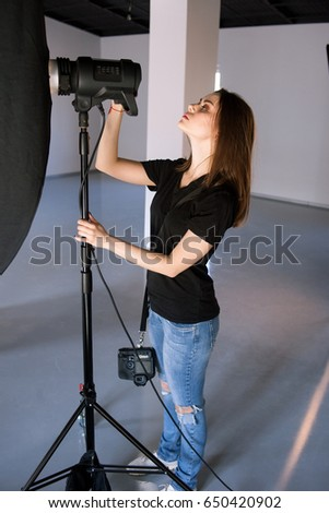Girl photographer adjust light in studio. Beautiful woman with camera is setting photographing equipment getting ready for a photo shoot - Shutterstock ID 650420902