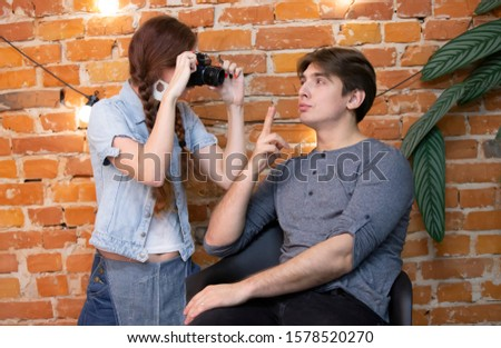 Girl photographer photographs a guy against a brick wall