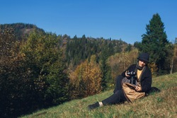 girl photographer sits on slope and takes camera out of backpack in mountains in autumn.