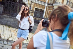 Girl photographer takes a photo of a model outdoors in the city