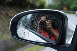 Girl photographer takes a selfie in the side mirror of the car. Enjoy the ride.