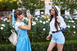 Girl photographer takes pictures of a model outdoors in the city